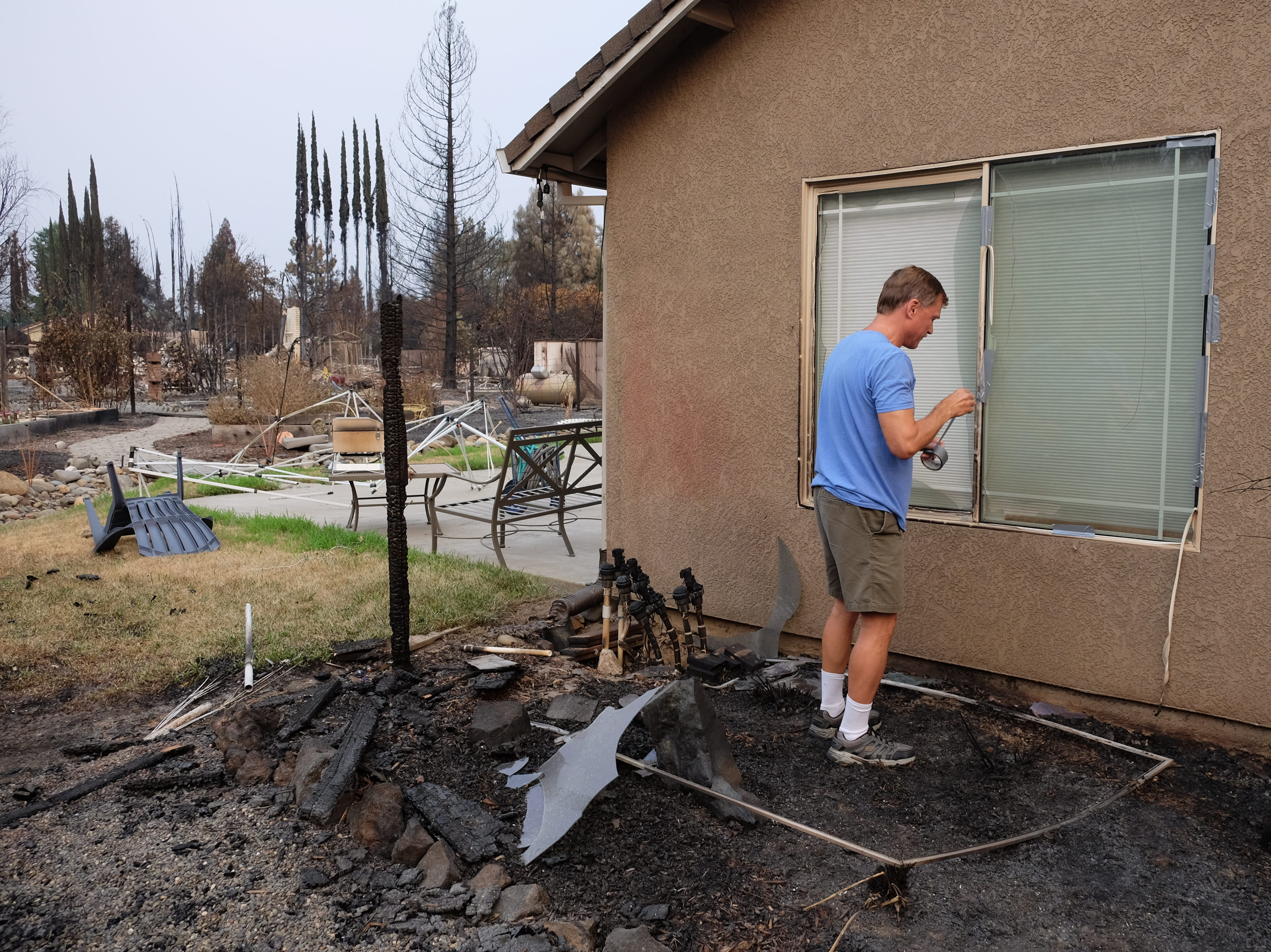 Bill Robinson tapes broken glass at their Redding home which avoided major damage from the Carr Fire. Many homes in their neighborhood were burned to the ground.