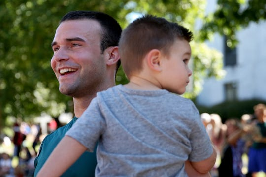 Tony Wilson, of Salem, holds his son, Eli Wilson, 2, after playing with his team, Chafing the Dream, in the Hoopla 3x3 basketball tournament near the Oregon State Capitol in Salem on Saturday, Aug. 4, 2018.