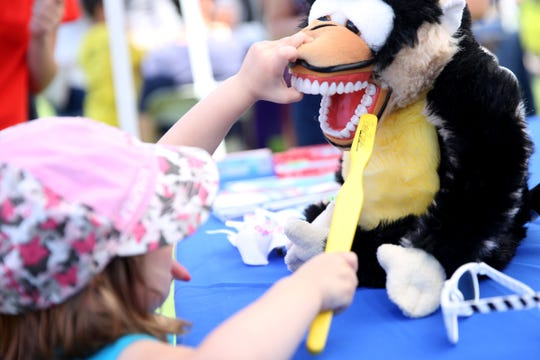 A child brushes a stuffed monkey's teeth at the Smile Keepers Dental booth during Riverfront Family Fest at Riverfront Park in Salem on Saturday, Aug. 4, 2018.
