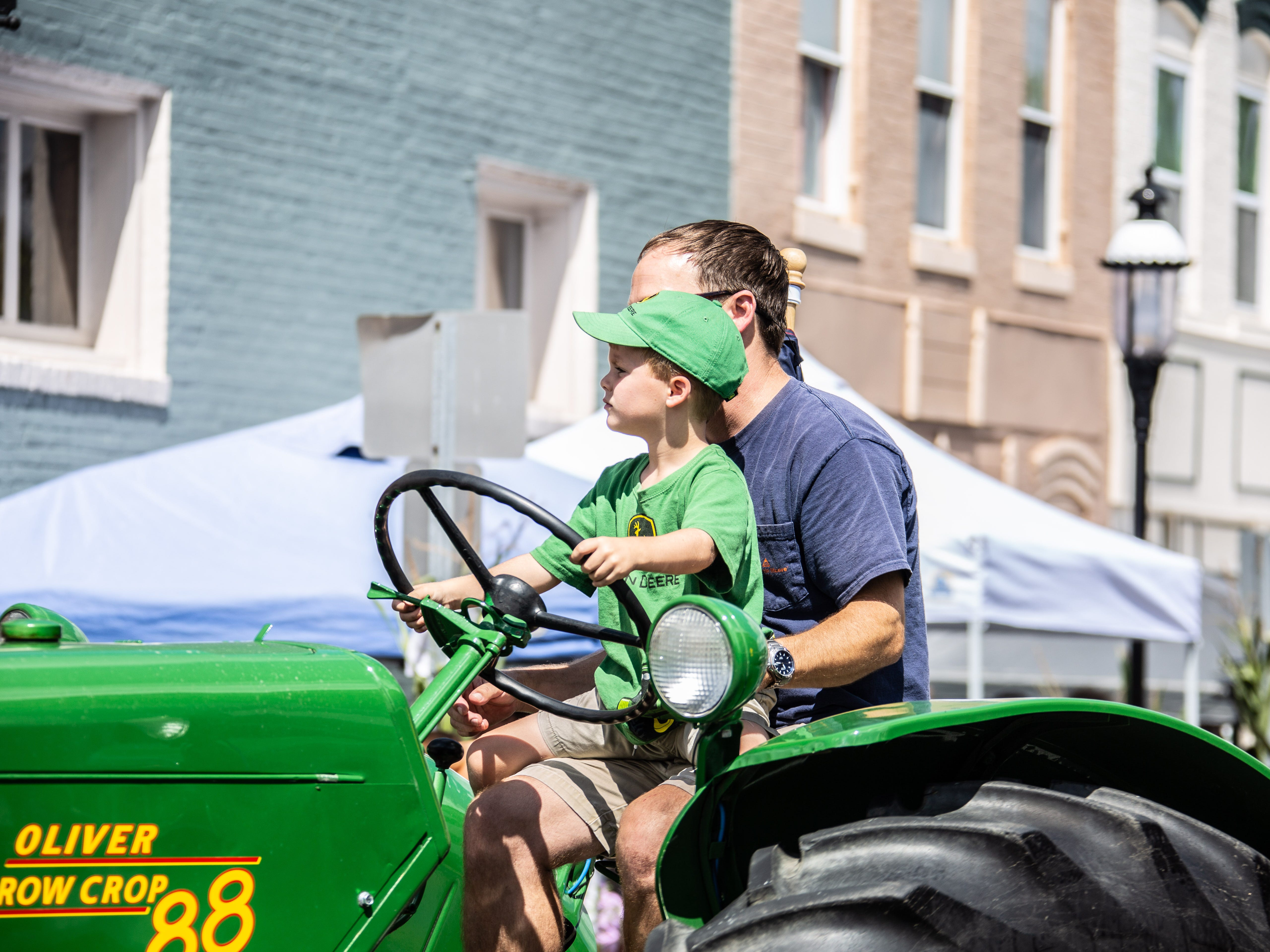A young farmer gets some help in steering his tractor during the parade at the 20th Blessing of the Combines honoring local farmers in Snow Hill.