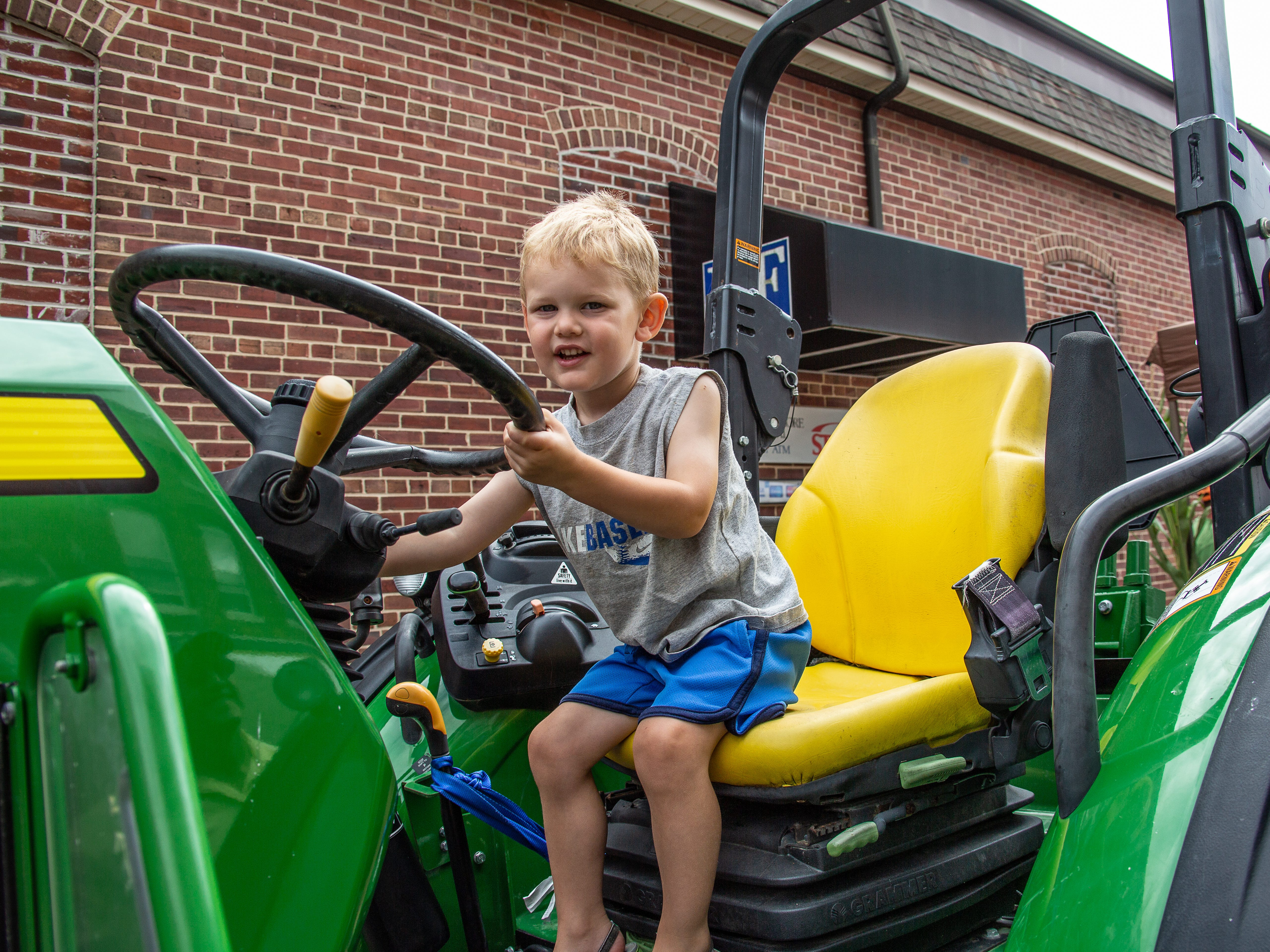 Emmitt Addis, 2, checks out a tractor at the Blessing of the Combines Saturday, Aug. 4, in Snow Hill.
