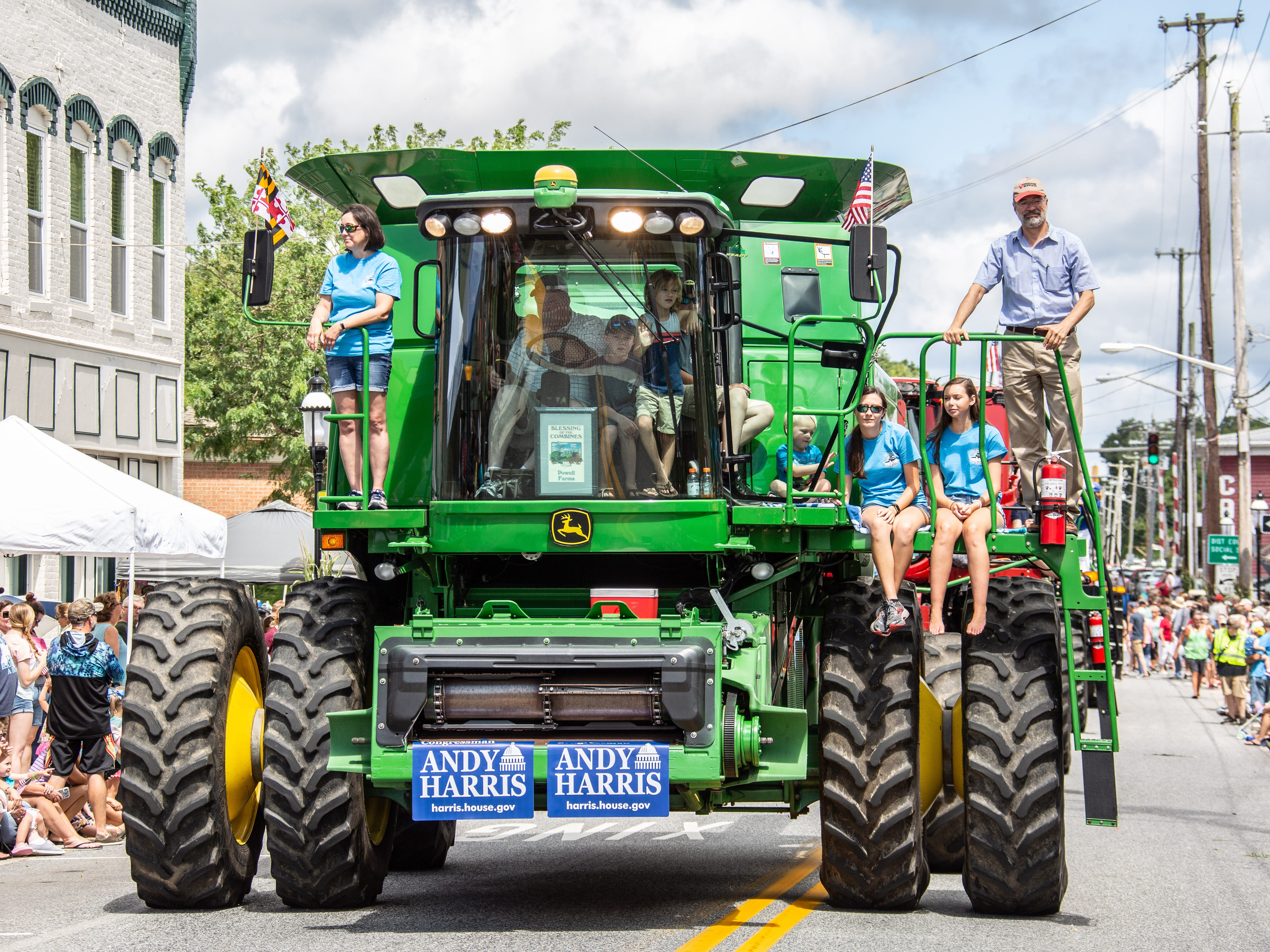 Children hitch a ride on a massive combine as it rolls past a packed crown during Snow Hill's 20th Blessing of the Combines.