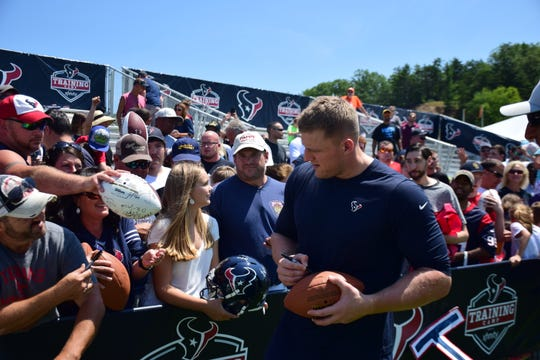 Houston Texans defensive end J.J. Watt signs a football for a fan during the NFL team's preseason camp on Saturday, Aug. 5, 2018, at the Greenbrier in White Sulphur Springs, W.Va.
