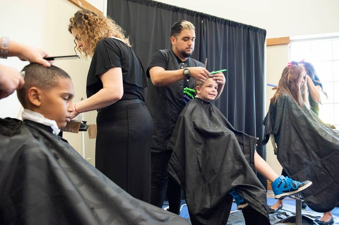"""It's an amazing discount.  Kids cuts are almost as much adult cuts these days,"" said Jennifer Brown Rios, not pictured, whose sons, Darian Brown, 12, left, and Jayden Rios, 5, center, get $5 haircuts by the stylists from Fusion Aveda Salon & Spa during the Back to School Family Expo on Saturday, August 4, 2018, at the Port St. Lucie Civic Center in Port St. Lucie. The event included many family-oriented and educational vendors, food trucks, musical entertainment, dance performances and arts and crafts activities. To see more photos, go to TCPalm.com."