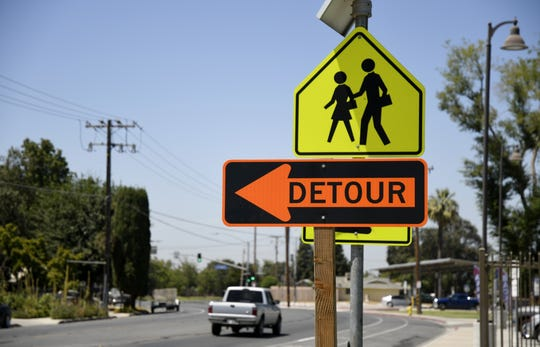 A detour sign near a crosswalk a Maple Elementary School in Tulare alerts drivers of roadwork on E Street on Friday, Aug. 3, 2018.