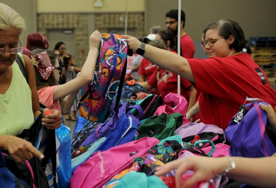 People pick up backpacks filled with school supplies Saturday, Aug. 4, 2018, at Project Back to School in the Ray Clymer Exhibit Hall at the MPEC.