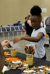 In this file photo, Cody Byrd gets pencils and her form signed at the Children's Aid Society booth at Project Back to School in the Ray Clymer Exhibit Hall at the MPEC.