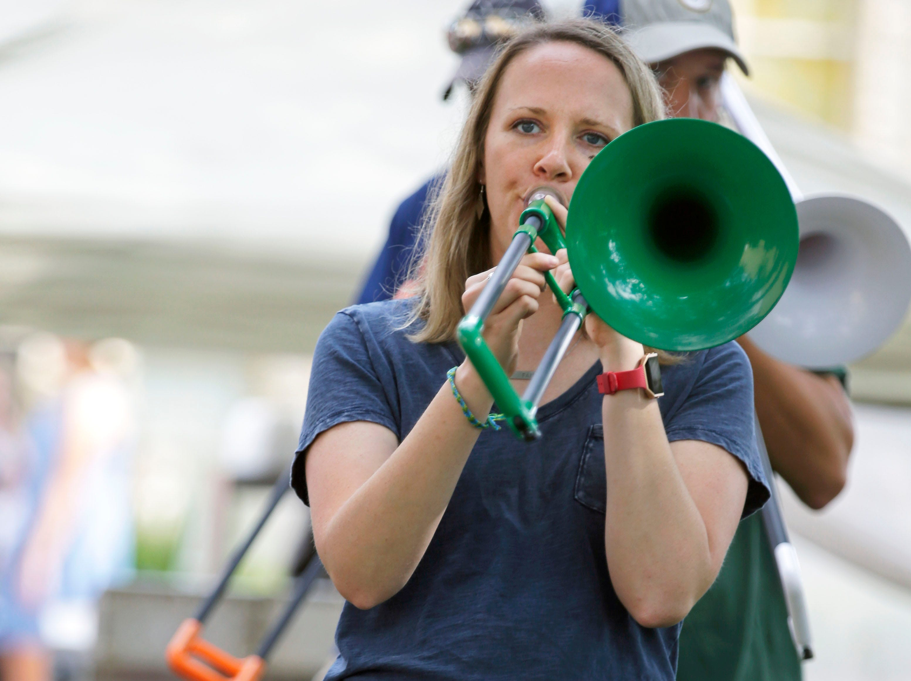 Charlotte Walters covers her ears as her mother, Emily, plays the trombone along with others gathered in the Grove for the pBone Jam as Mile 6, the Mile of Music festival takes place Saturday, August 4, 2018, in Appleton, Wis.