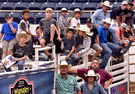 Boys watch mothers climb into their chutes during Moms' Steer Riding at the Taylor County Coliseum.