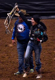 Esperanza Leffew of Phoenix celebrates her championship ride in the Moms' Steer Riding.