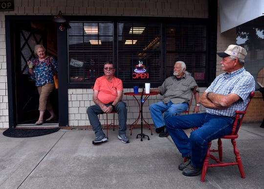 Mary Beth Ahrens steps out of Cup of Joe Vintage Coffee Shop on Thursday in Winters, looking toward her husband Ted (right) who then stood and accompanied his wife to their car. Joe Meyers (center) and Steven Joeris continued to enjoy the cool morning, watching the traffic pass on U.S. Highway 83 as they conversed.