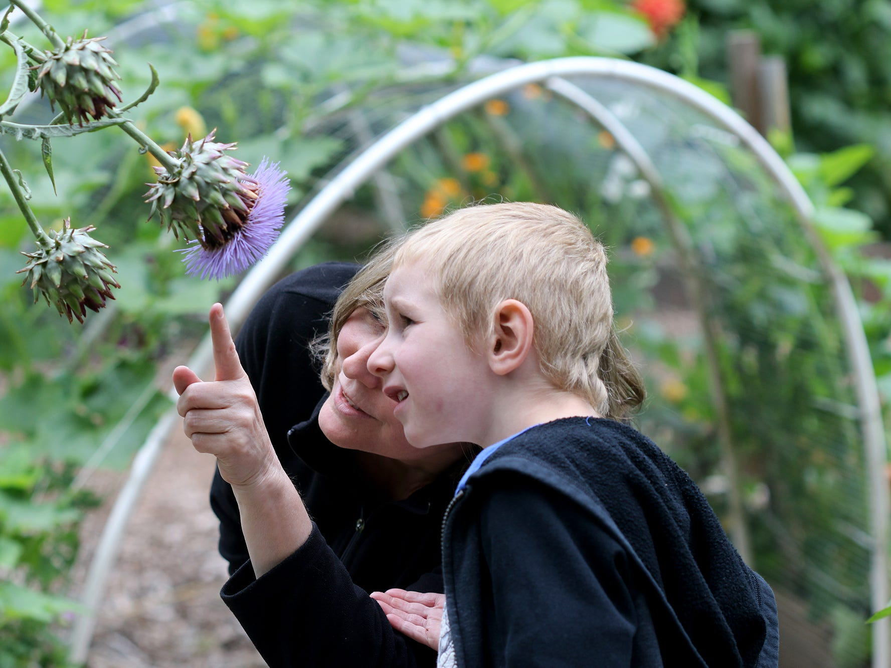 Debbie Anne, of Poulsbo, shows her grandson Keegan Lockwood, 6, a bee at Anna Smith Garden on Saturday, August 4, 2018.
