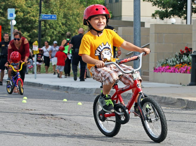 """Moises Valadez, 7, of Des Moines rides his free bike during the """"Bike Back to School"""" event at the Des Moines Police Station, 25 East First St, on Saturday, August 4, 2018 presented in partnership by the Des Moines Police Department, Des Moines Bike Collective, Fareway Foods and Des Moines Parks and Recreation."""