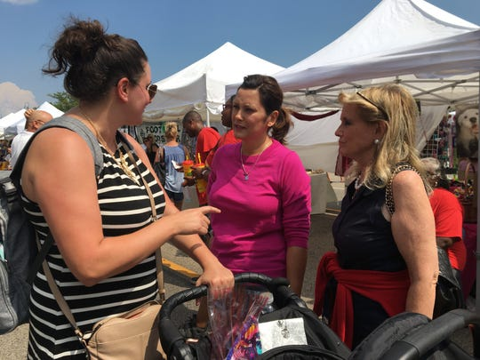 Democrat candidate for Governor Gretchen Whitmer, center, and U.S. Rep. Debbie Dingell, D-Dearborn, right speak with a woman while out campaigning at the Allen Park Street Fair on Friday, August 3, 2018.