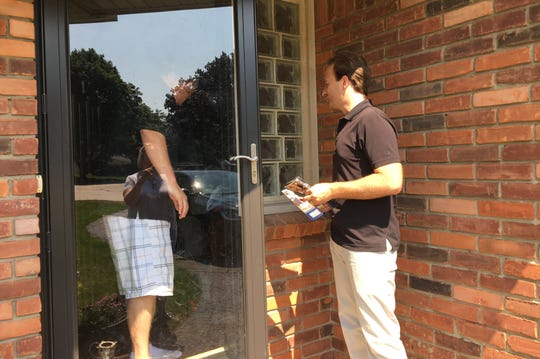 Lt. Gov. Brian Calley, Republican candidate for Governor, right, speaks with a man as he knocks on doors while campainging in a neighborhood in Farmington on Sunday, August 5, 2018.