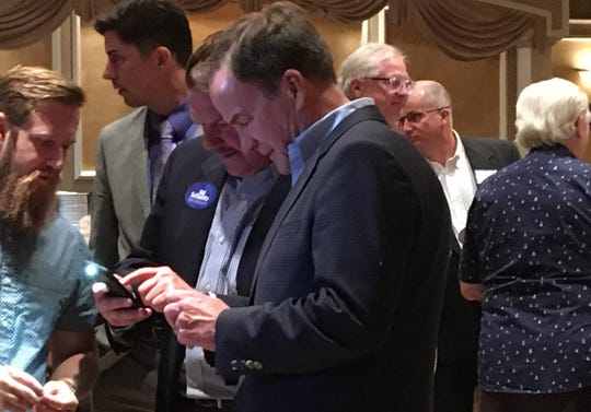 Attorney General Bill Schuette, a Republican candidate for Governor, huddles with state Rep. Peter Lucido, R-Shelby Township, left, during a rally Thursday, August 2, 2018 at Penna's Little Villa Banquet Center in Clinton Township.