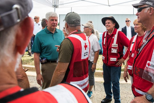Michigan Gov. Rick Snyder talks with American Red Cross volunteers at the water distribution center at Parchment High School in Parchment, Mich., on Sunday, Aug. 5, 2018.