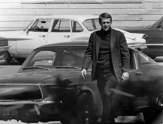 "Steve McQueen, starring in the title role of ""Bullitt,"" steps out of his car after a 140-mph pursuit through the hilly streets of San Francisco."
