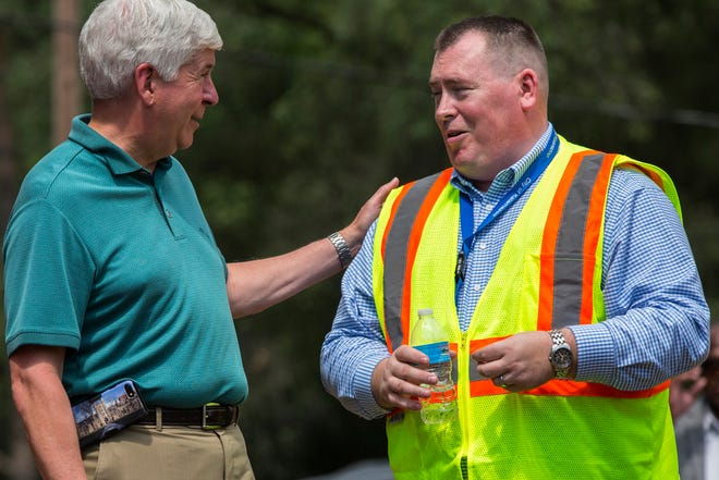 Michigan Gov. Rick Snyder, left, talks to Kalamazoo Public Services Director James Baker as the governor tours the new water connection on G Avenue that will hook the city of Parchment water supply up with the city of Kalamazoo in Parchment, Mich., on Sunday, Aug. 5, 2018.