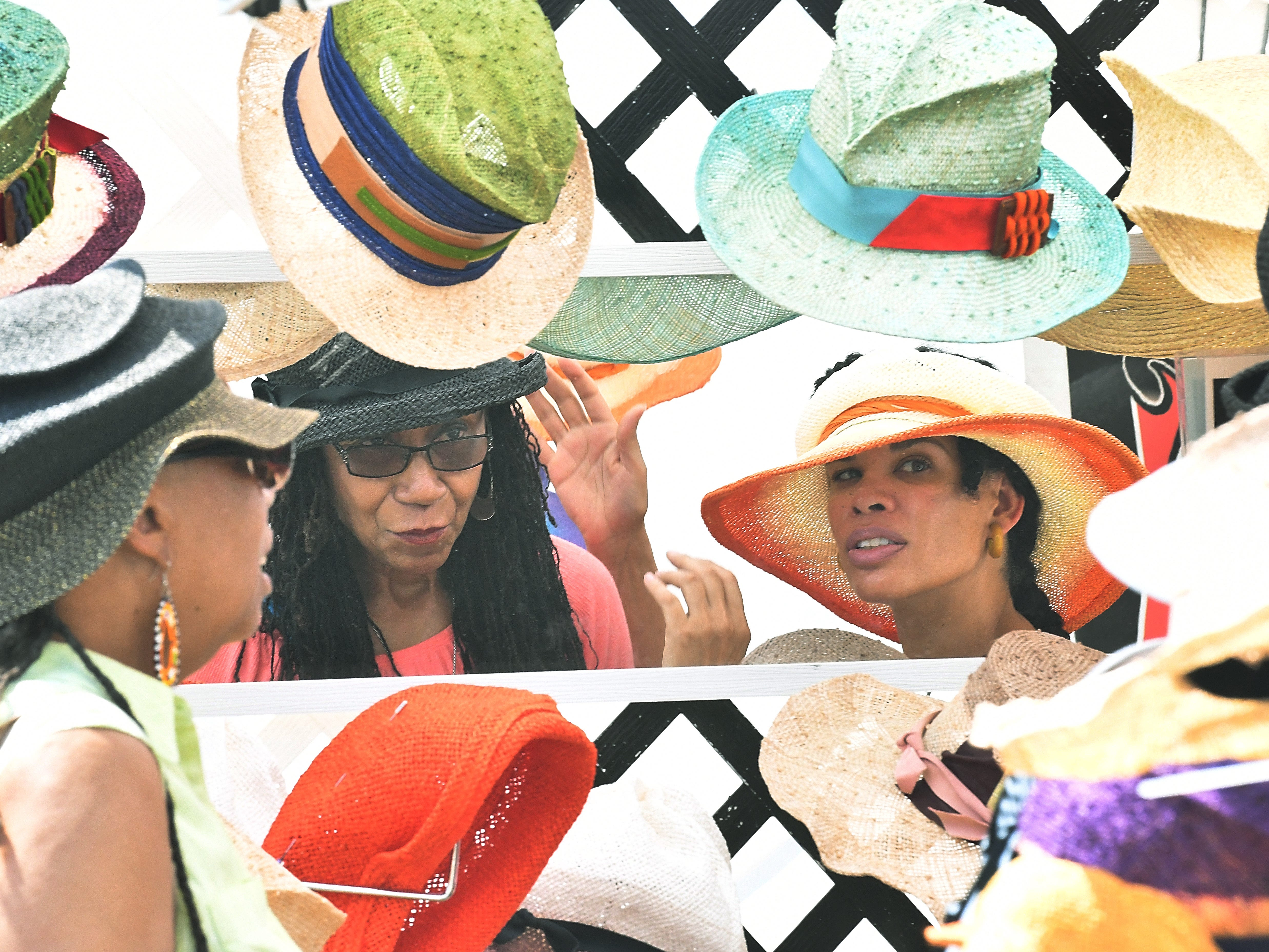 Sherallyn Buyck gets some help from Ella Isaac of L.I.P.S. Hats (Living In Perfect Style) trying on hats at her booth at the Belle Isle Art Fair.
