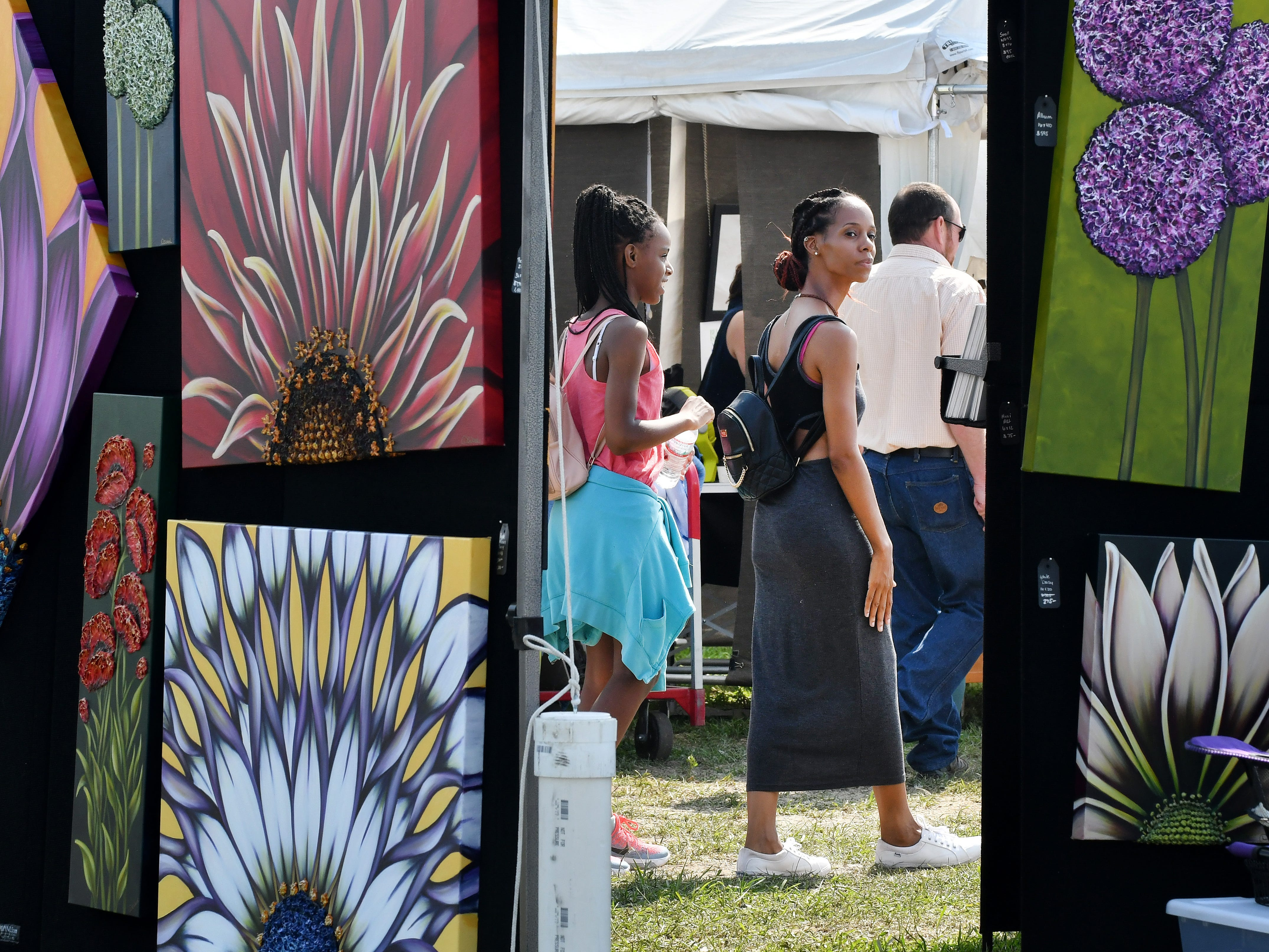 Autumn Brown, 11 and Nakia Camp wonder past the artwork of Denise Cassidy Wood while visiting the Belle Isle Art Fair in Detroit on Aug. 5, 2018.
