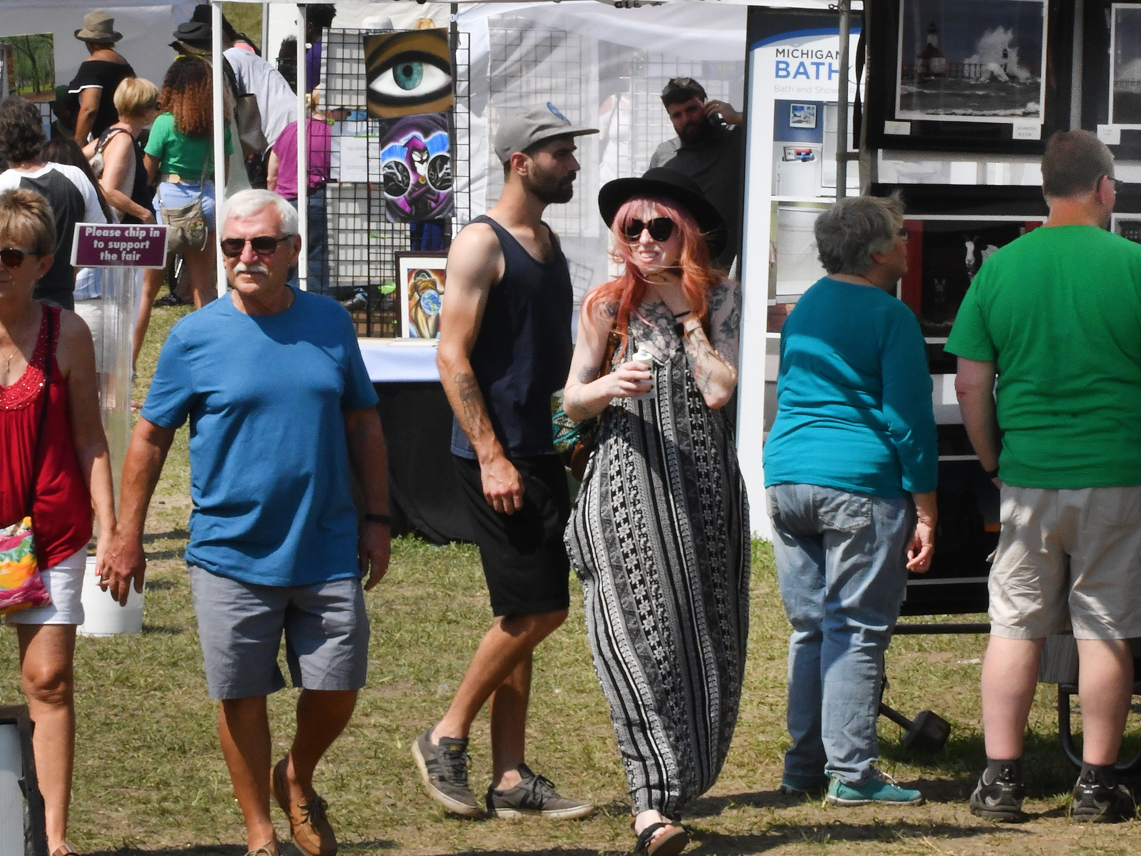 Fairgoers wander through the tents near the fountain at the third annual Belle Isle Art Fair.