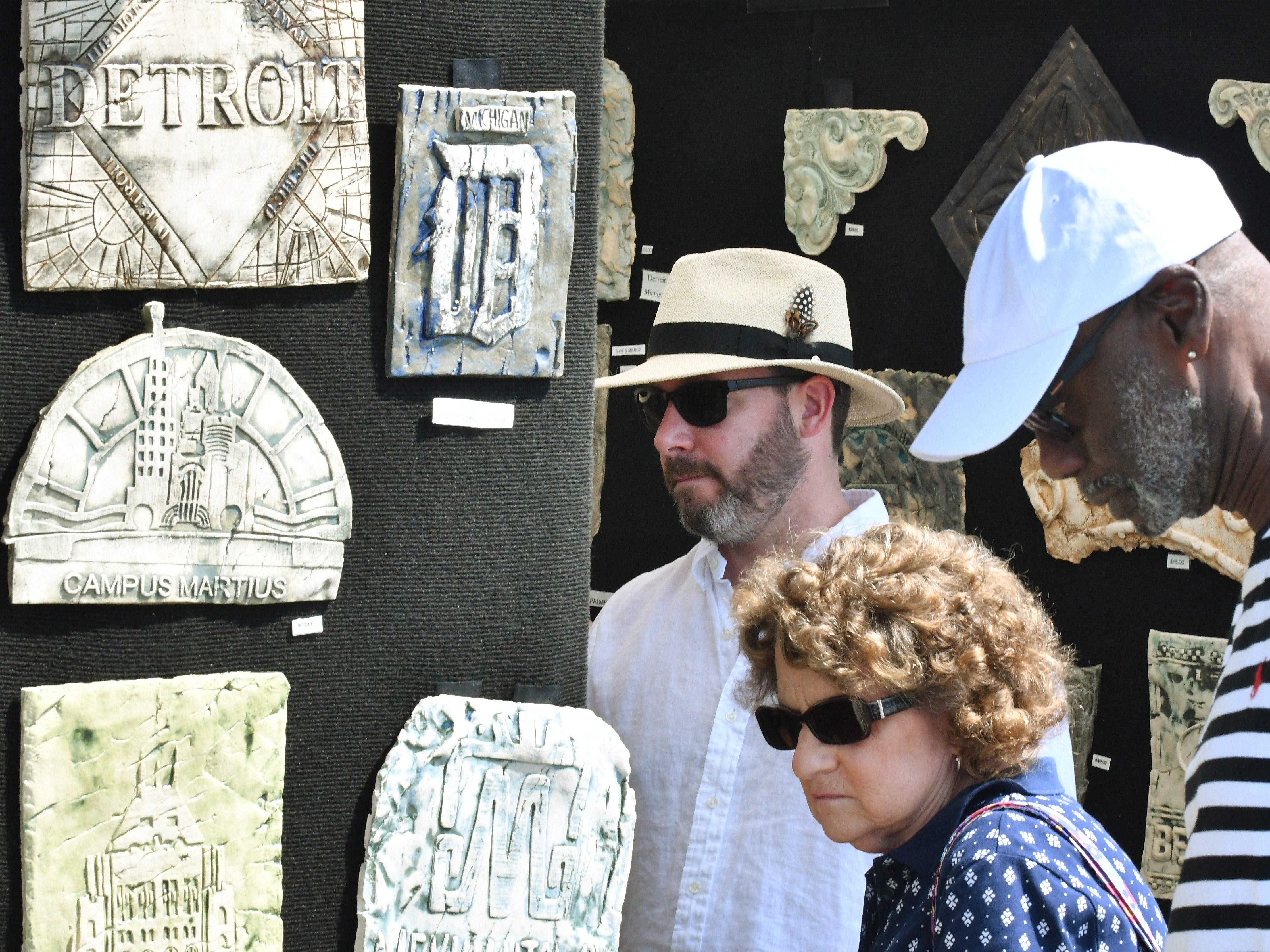 Fairgoers wander past the work of artist Debbie La Pratt whose clay pieces are created from elements found on such things as manhole covers, iron fences, and ceiling tiles and is signed with her fingerprint, leaving her mark on our history.