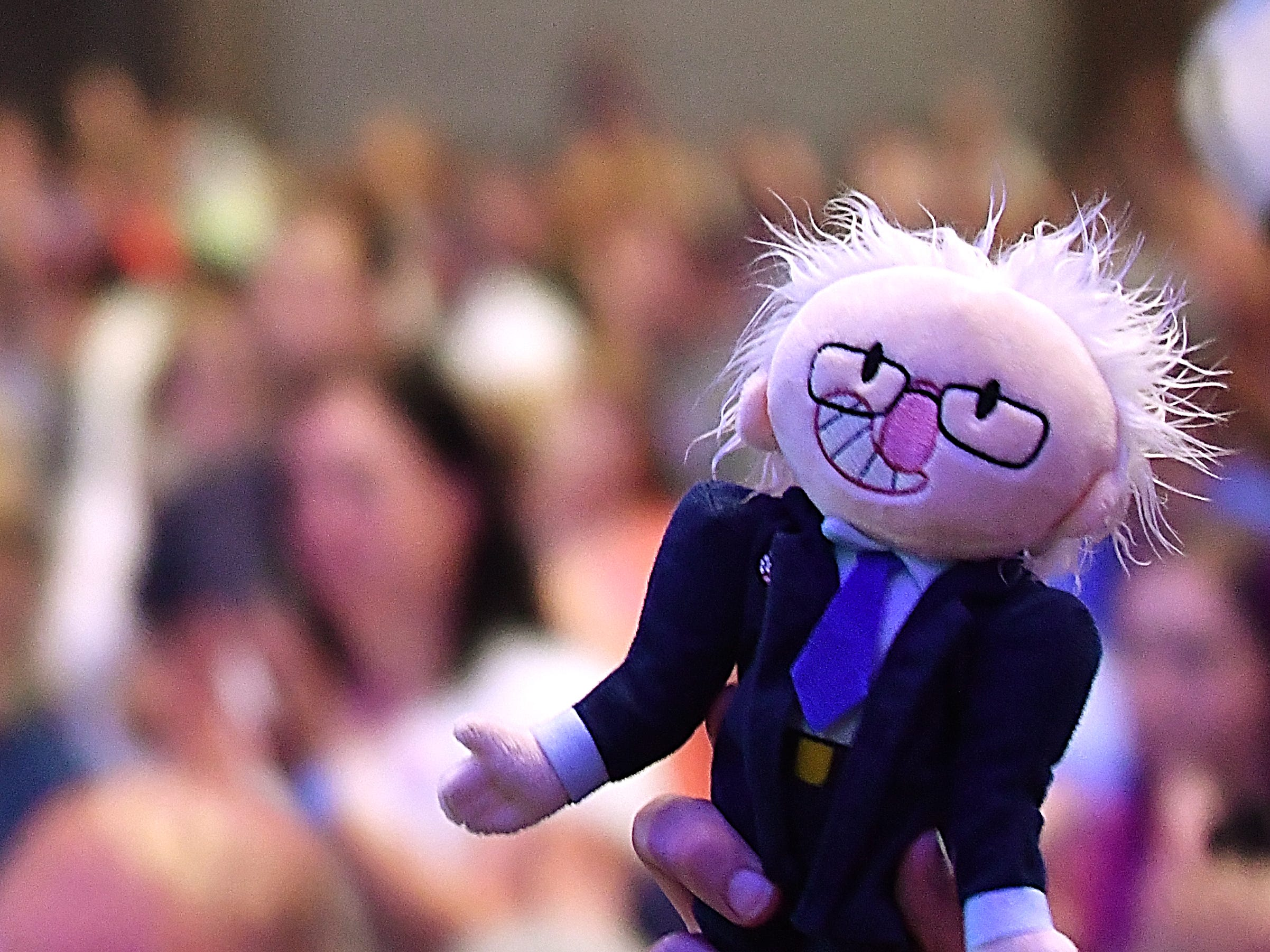 A Bernie Sanders stuffed doll is lifted into the air by a member of the crowd.