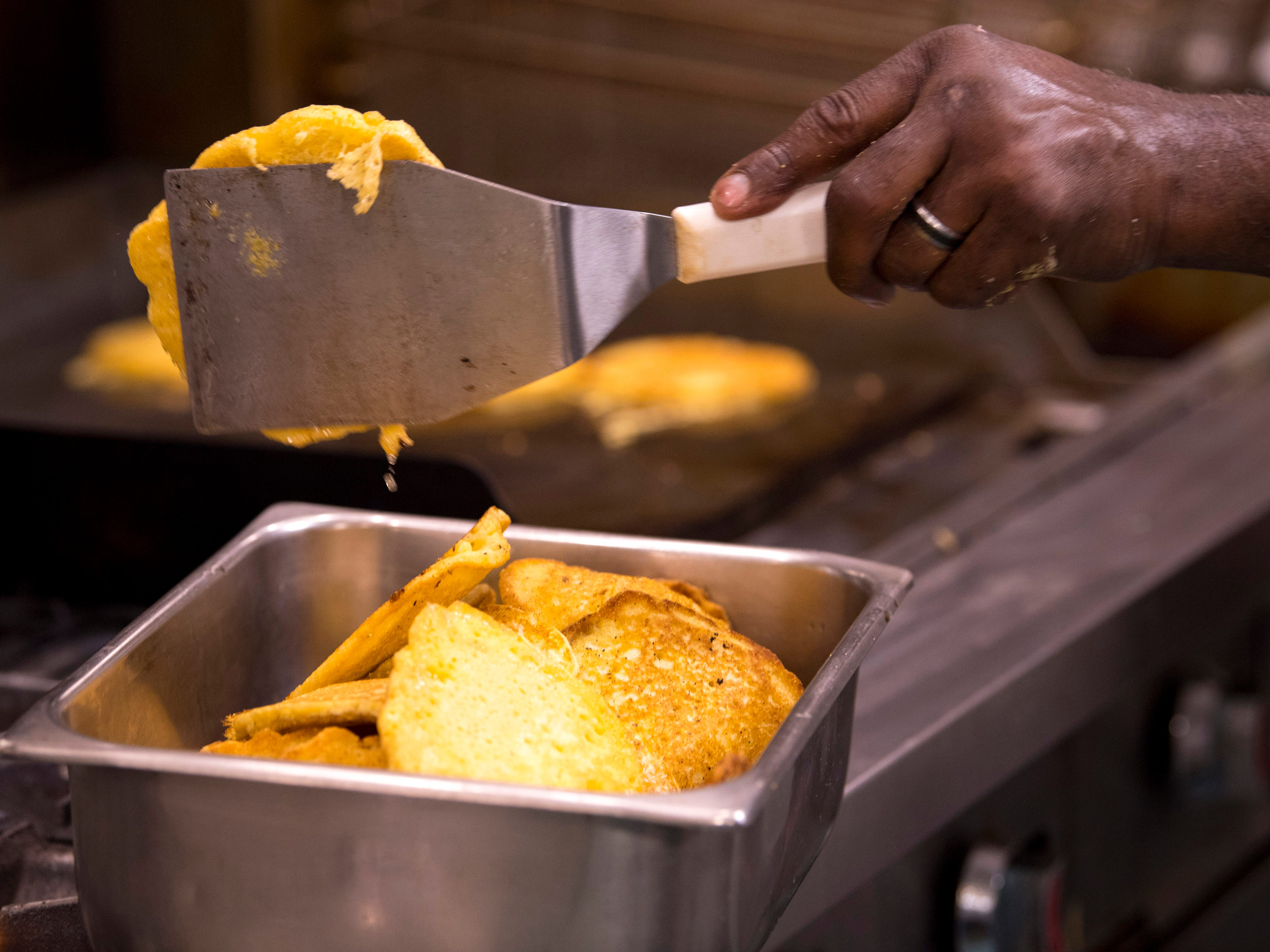 Gary Boyd flips corn cakes into a container at Gatrick's Bar-B-Que and Fine Dishes Sunday morning.