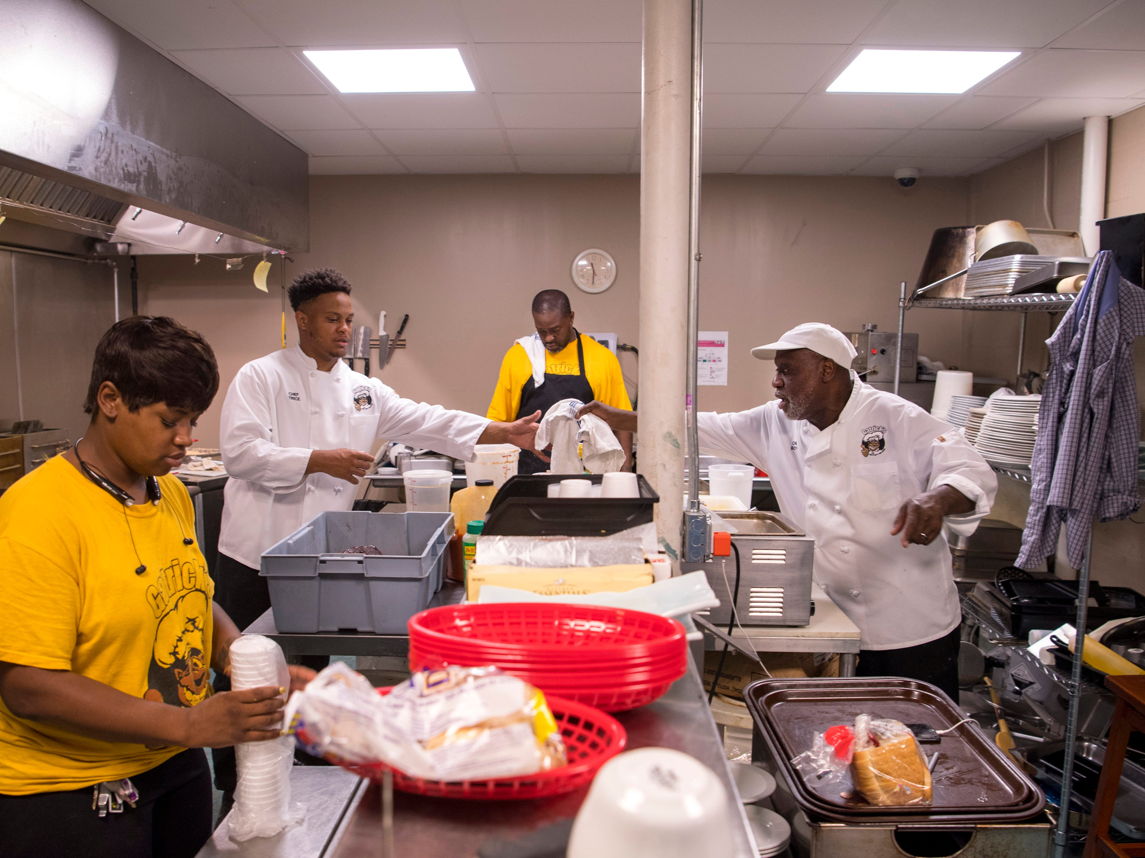 "The Gatrick's Bar-B-Que and Fine Dishes kitchen staff, from left, Donyea Brown, Stanley Trice, Antwan Henry and Gary ""Gatrick"" Boyd, prepare the food for their customers Sunday morning."