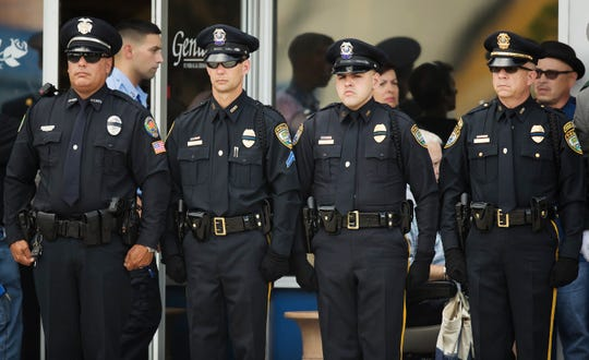 Fort Myers police officers stand in honor outside the viewing services for fallen Fort Myers police Officer Adam Jobbers-Miller on Sunday at the Gendron funeral home in Fort Myers, Florida. Jobbers-Miller was shot and killed recently while trying to apprehend a suspect.
