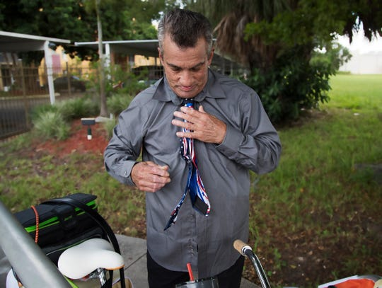 Roger Pope readies himself to attend the viewing of fallen Fort Myers police Officer Adam Jobbers-Miller on Sunday at the Gendron funeral home in Fort Myers, Florida. Pope rode his daughter's bike 20 miles to get to the service. Jobbers-Miller was shot and killed recently while trying to apprehend a suspect.