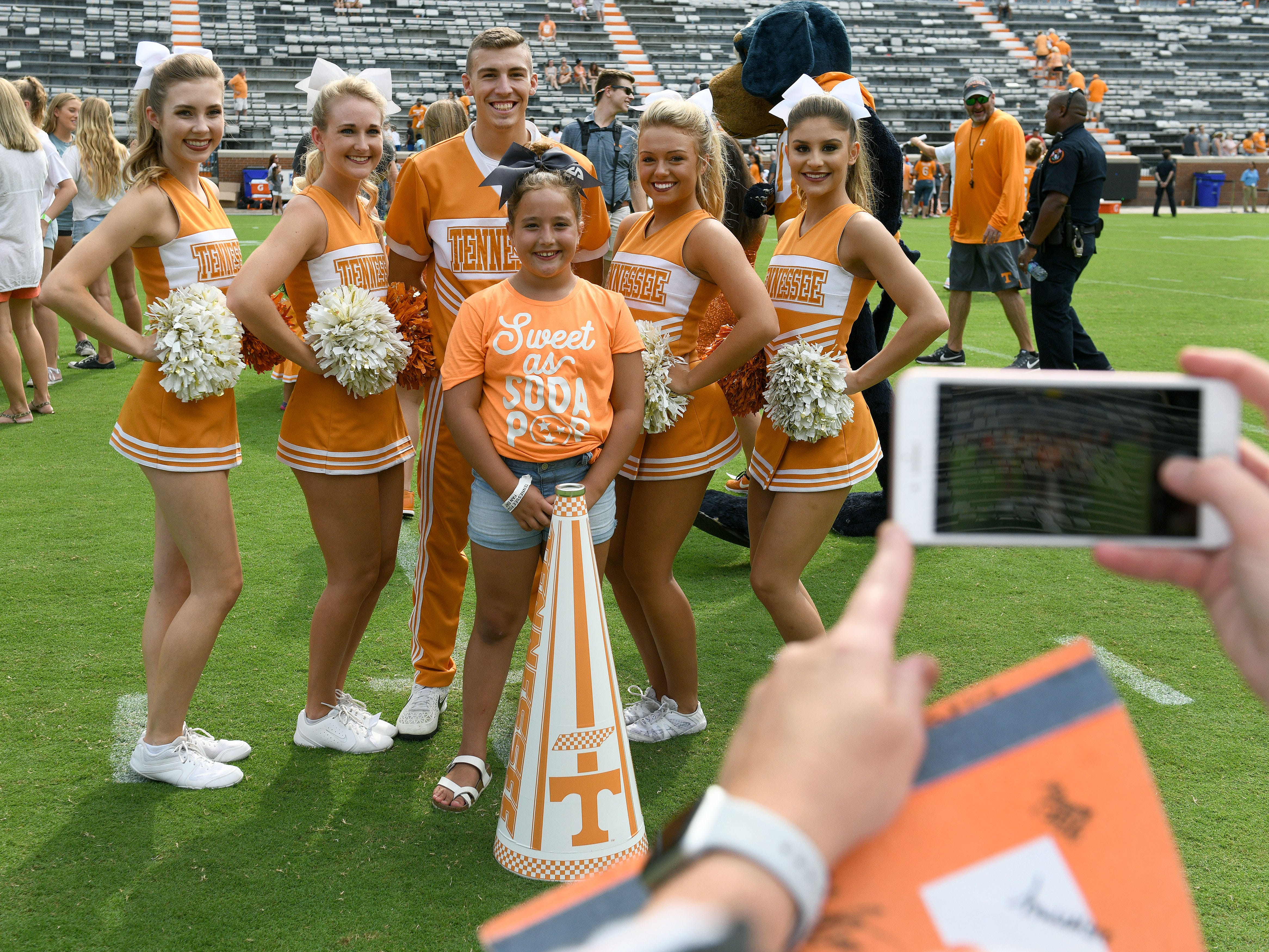 A UT fan gets her picture made with cheerleaders at the conclusion of practice as part of Fan Day in Neyland Stadium Sunday, August 5, 2018.
