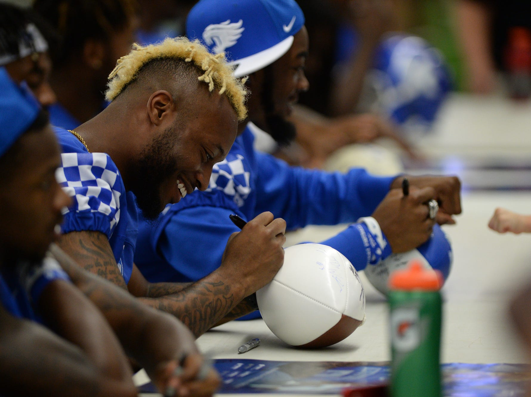 Safety Mike Edwards autographs a football during the UK football Fan Day at Nutter Field House in Lexington, Kentucky on Saturday, August 4, 2018.