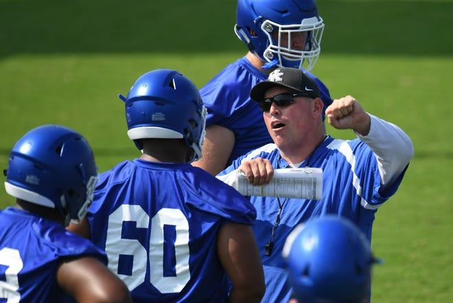 Former Kentucky offensive line coach John Schlarman died on Thursday.