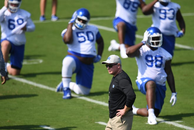 Head coach Mark Stoops watches warmups during the UK football Fan Day at Nutter practice field in Lexington, Kentucky on Saturday, August 4, 2018.