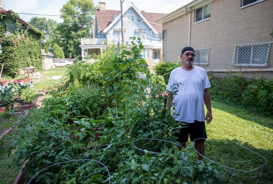 """Bernie Grosso, 61, of Milwaukee and a Marine Corps veteran from 1974-'76, stands next to his garden plot that has a variety of tomatoes, bell peppers, jalapenos, and banana peppers. Grosso explains that the garden relieves a lot of his stress. """"It's our little getaway,"""" he said."""