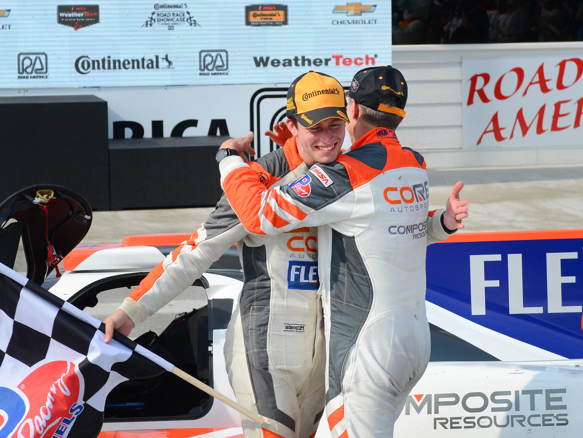 Colin Braun gets a hug from co-driver Jonathan Bennett after winning the the Continental Tire Road Race Showcase on Sunday, August 5, 2018, at Road America in Elkhart Lake, Wis.