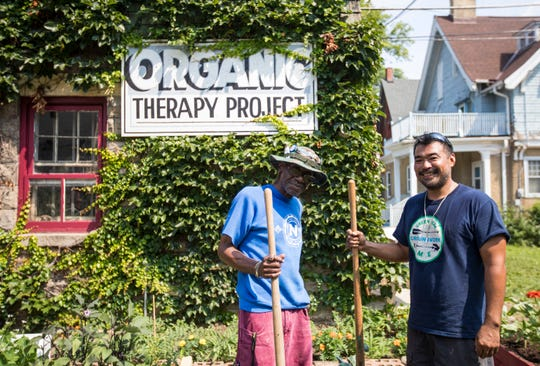 William Sims, left, a Vietnam veteran, and Brian Sales, leader of the Milwaukee chapter of Green Veterans, stand in the garden on West Wells Street cared for by veterans. Sims is the director of the organic therapy program while Sales is dealing with PTSD after serving two tours inIraq and one in Kosovo in the Army.