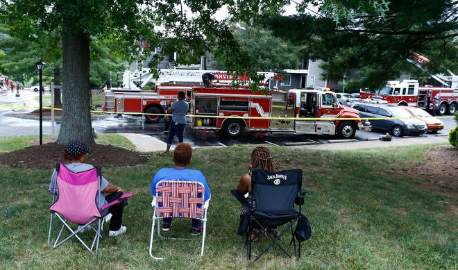 Residents sit in lawn chairs as they watch firefighters during a fire at Timberlake Village Apartment on Sunday, Aug. 5, 2018, in Antioch.