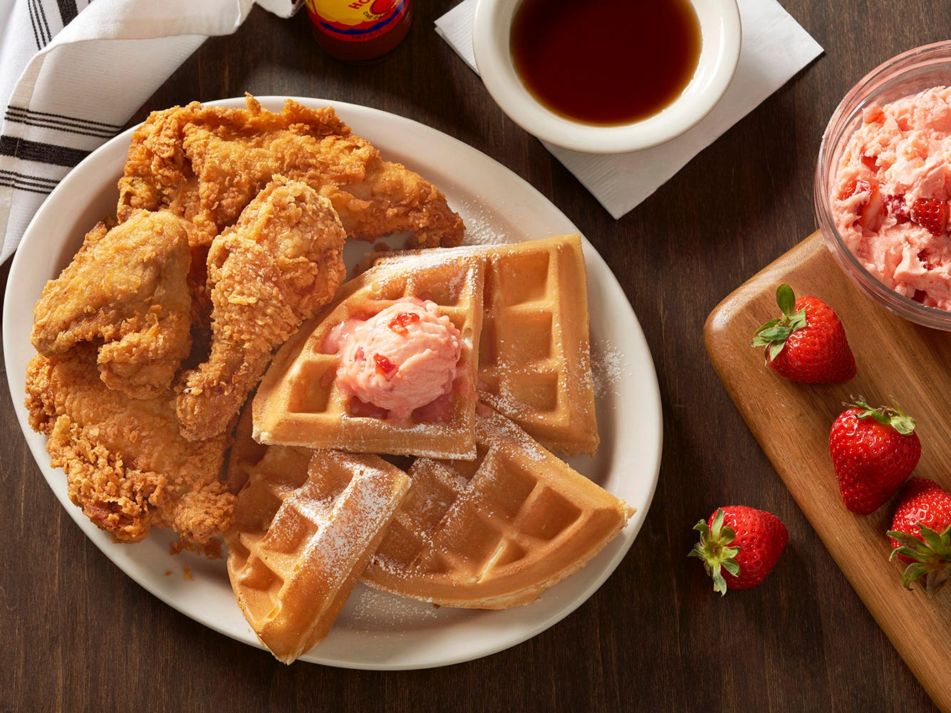 Metro Diner's Fried Chicken & Waffle dish features a Belgian waffle topped with sweet, strawberry butter and half a fried chicken served with the diner's signature sweet and spicy sauce.