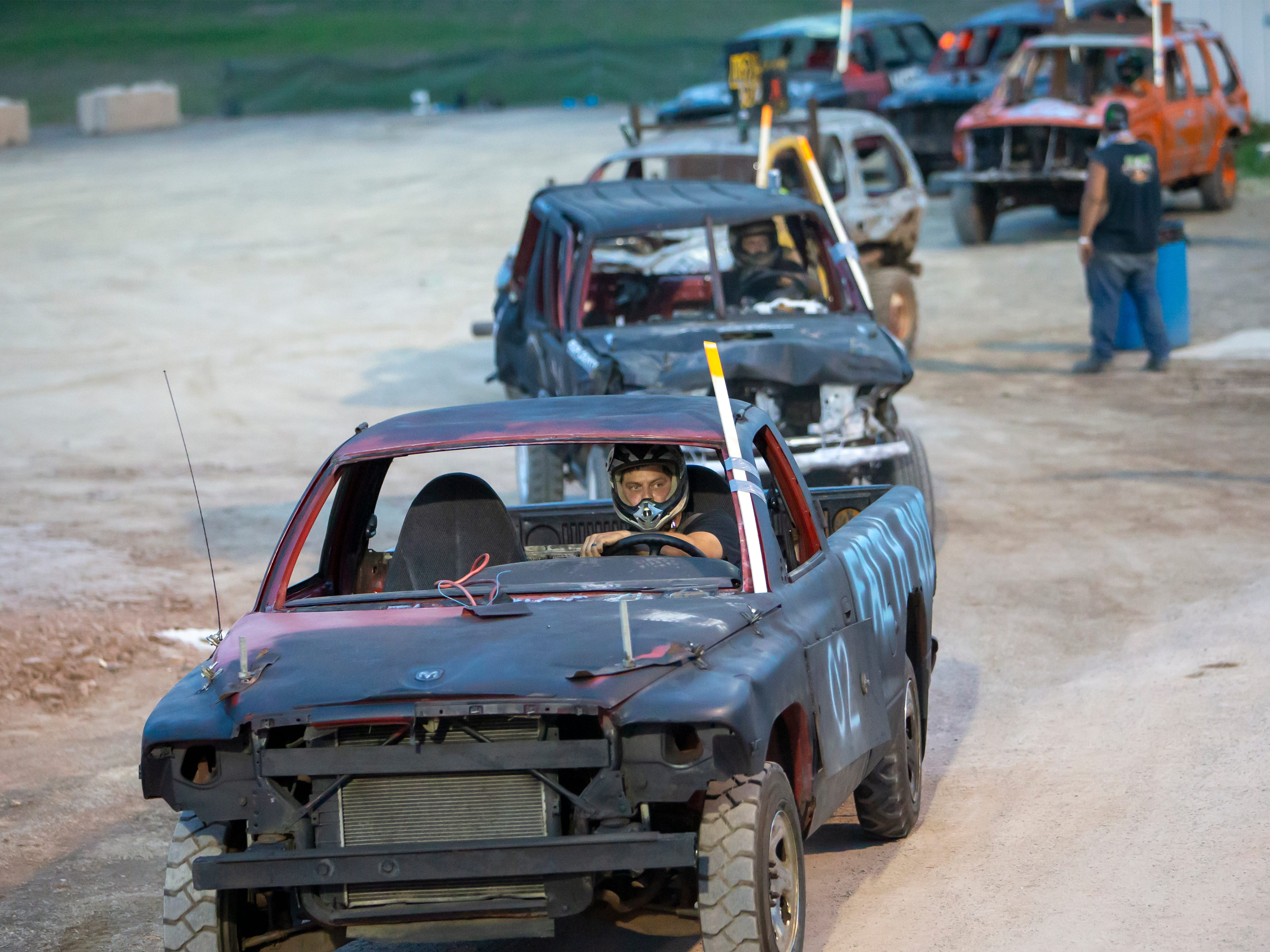 Drivers line into position for the demolition derby during the Winnebago County Fair on Saturday, Aug. 4, 2018.