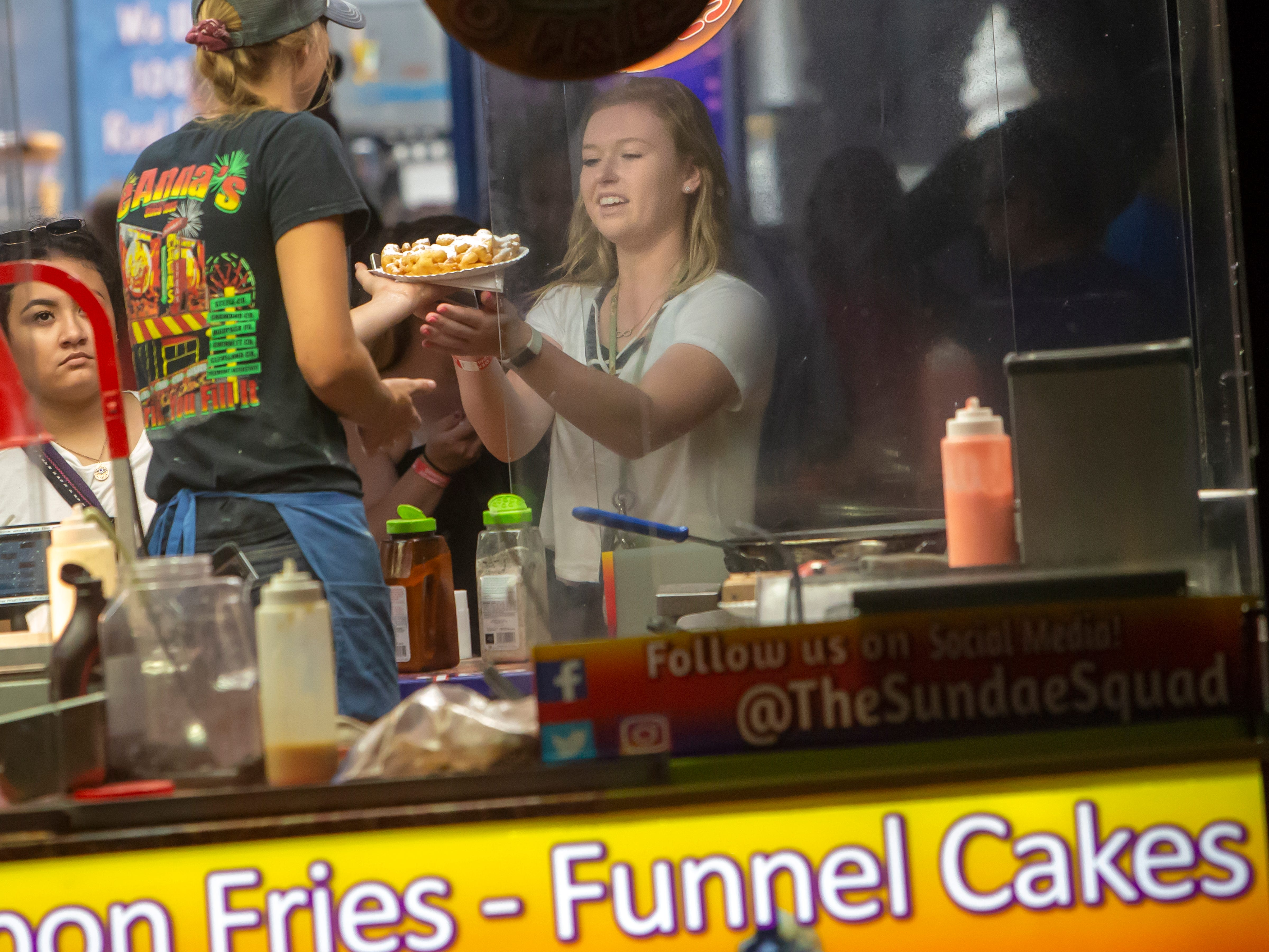 Tierney Ecklund orders a funnel cake Saturday during the Winnebago County Fair on Saturday, Aug. 4, 2018.