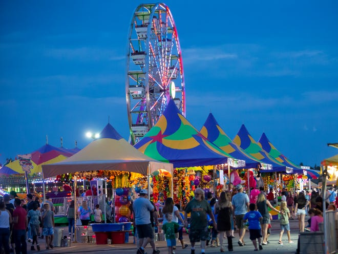 People walk through the carnival during the Winnebago County Fair on Saturday, Aug. 4, 2018.