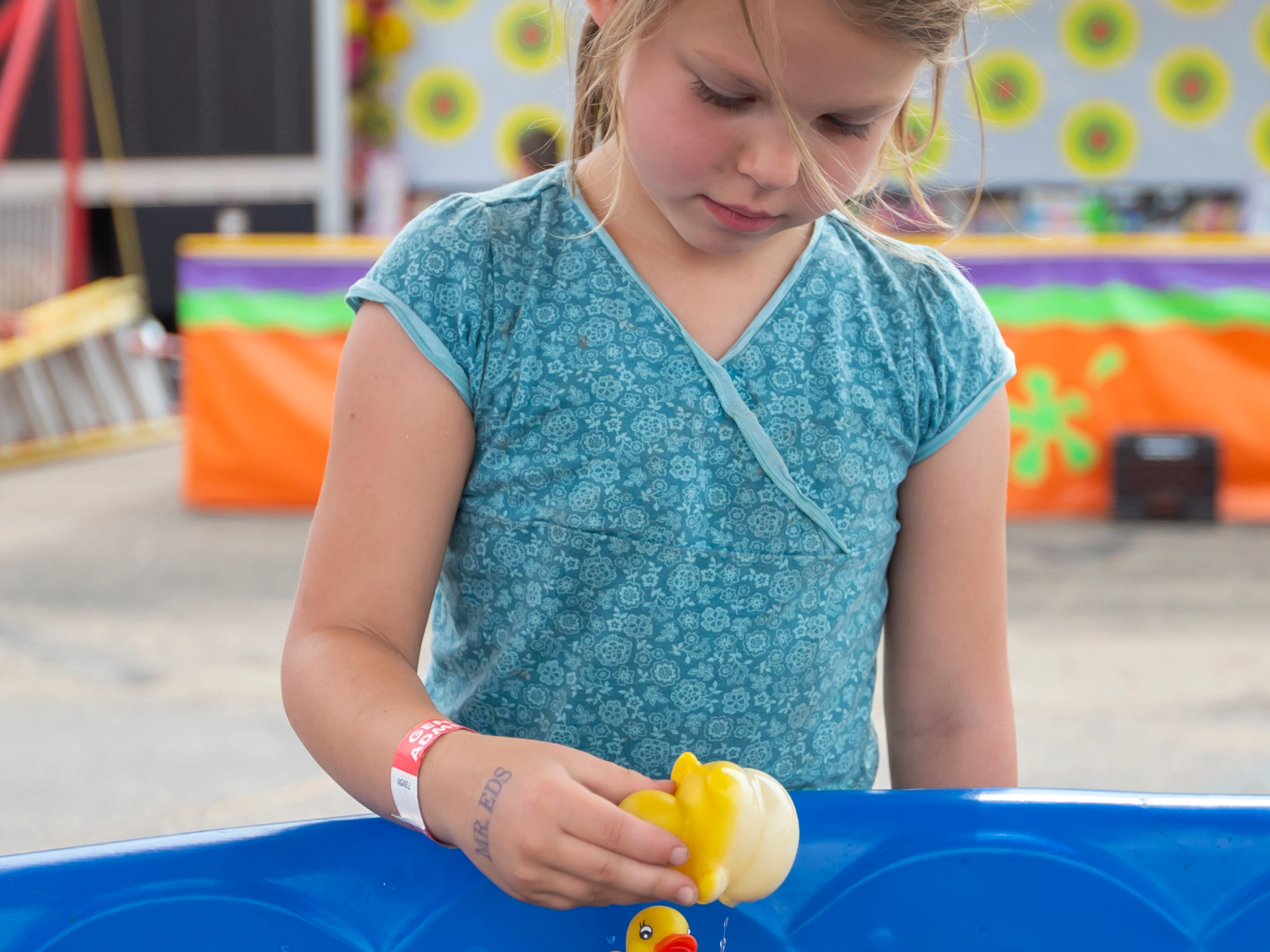 Bella Drheim plays a carnival game pick a duck for a prize during the Winnebago County Fair on Saturday, Aug. 4, 2018.