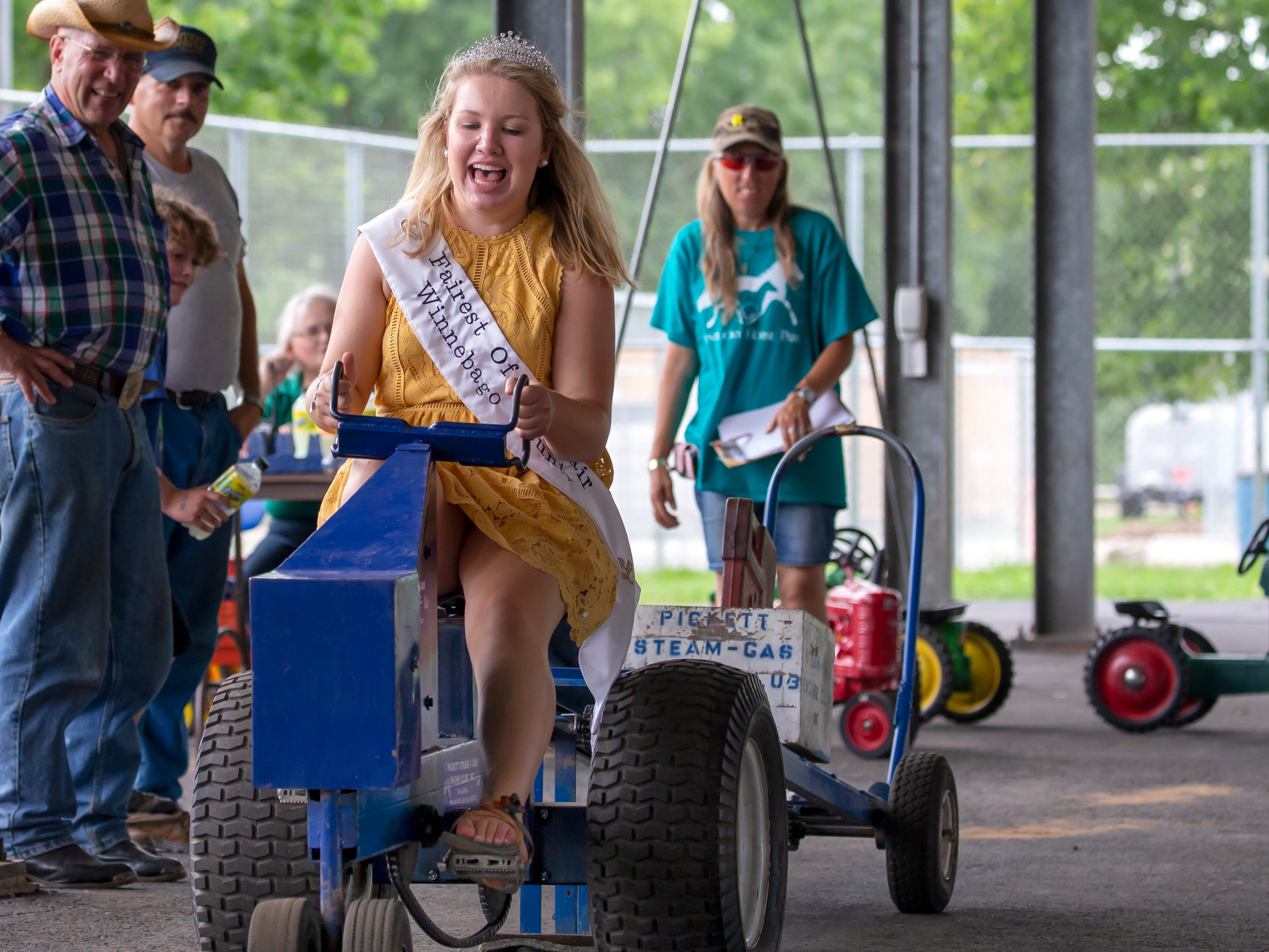 Miss Fairest of the Fair of Winnebago County peddles hard on a kid's truck pull during the Winnebago County Fair on Saturday, Aug. 4, 2018.