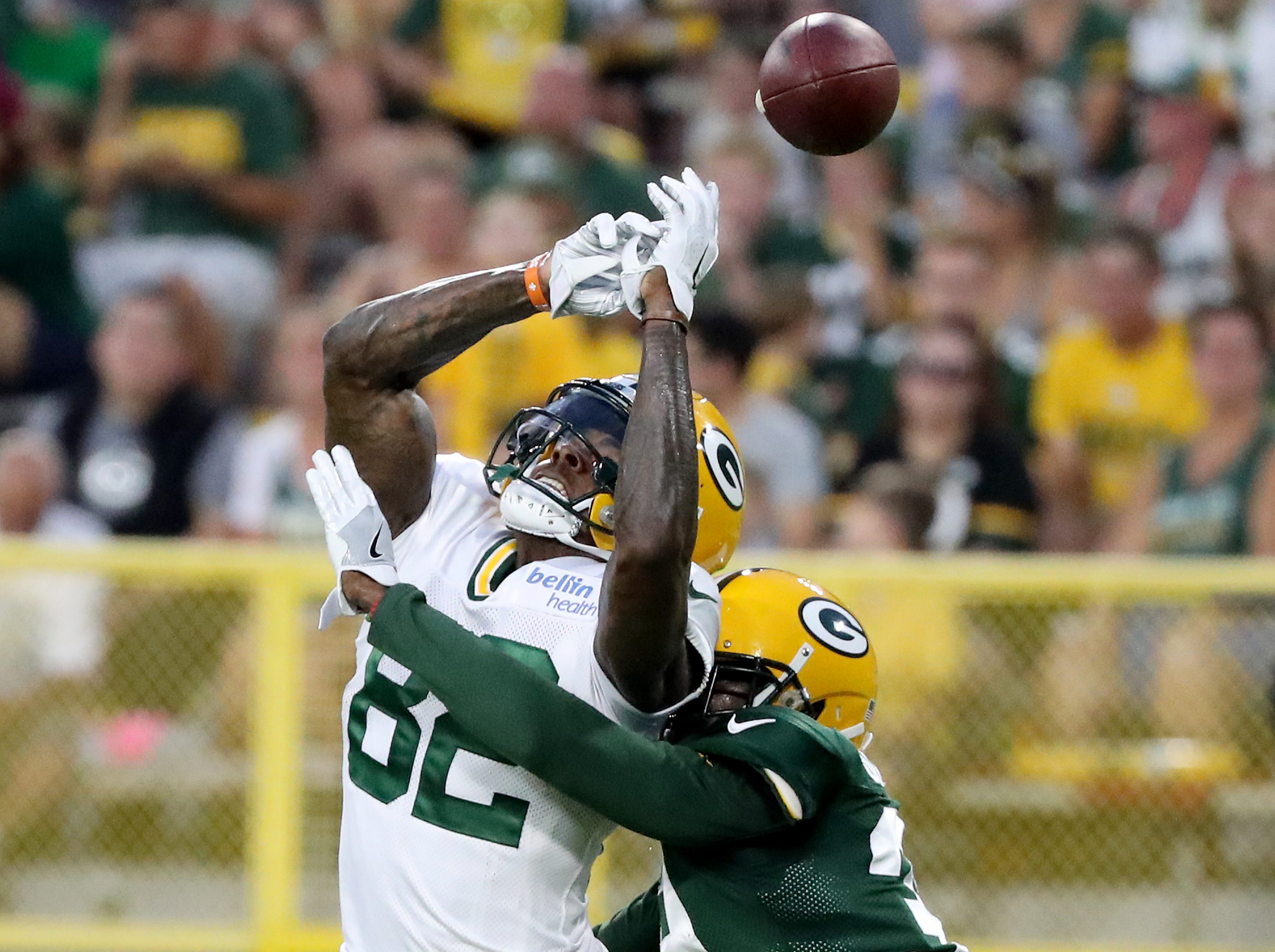 Green Bay Packers defensive back Tramon Williams (38) breaks up a pass to wide receiver J'Mon Moore (82) during Green Bay Packers Family Night  Saturday, August 4, 2018 at Lambeau Field in Green Bay, Wis.,