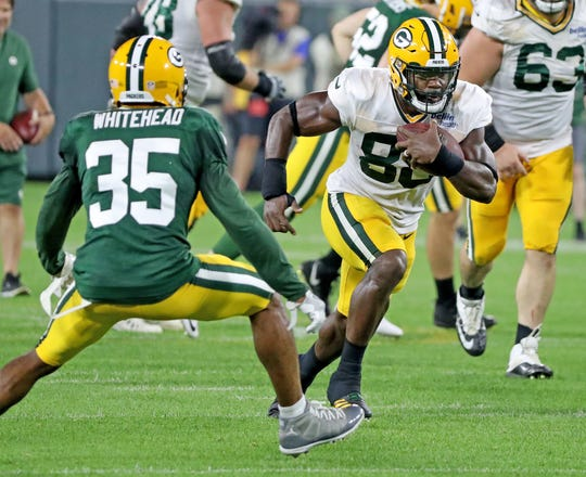 Green Bay Packers running back Ty Montgomery (88) runs past safety Jermaine Whitehead (35) during Green Bay Packers Family Night  Saturday, August 4, 2018 at Lambeau Field in Green Bay, Wis.,