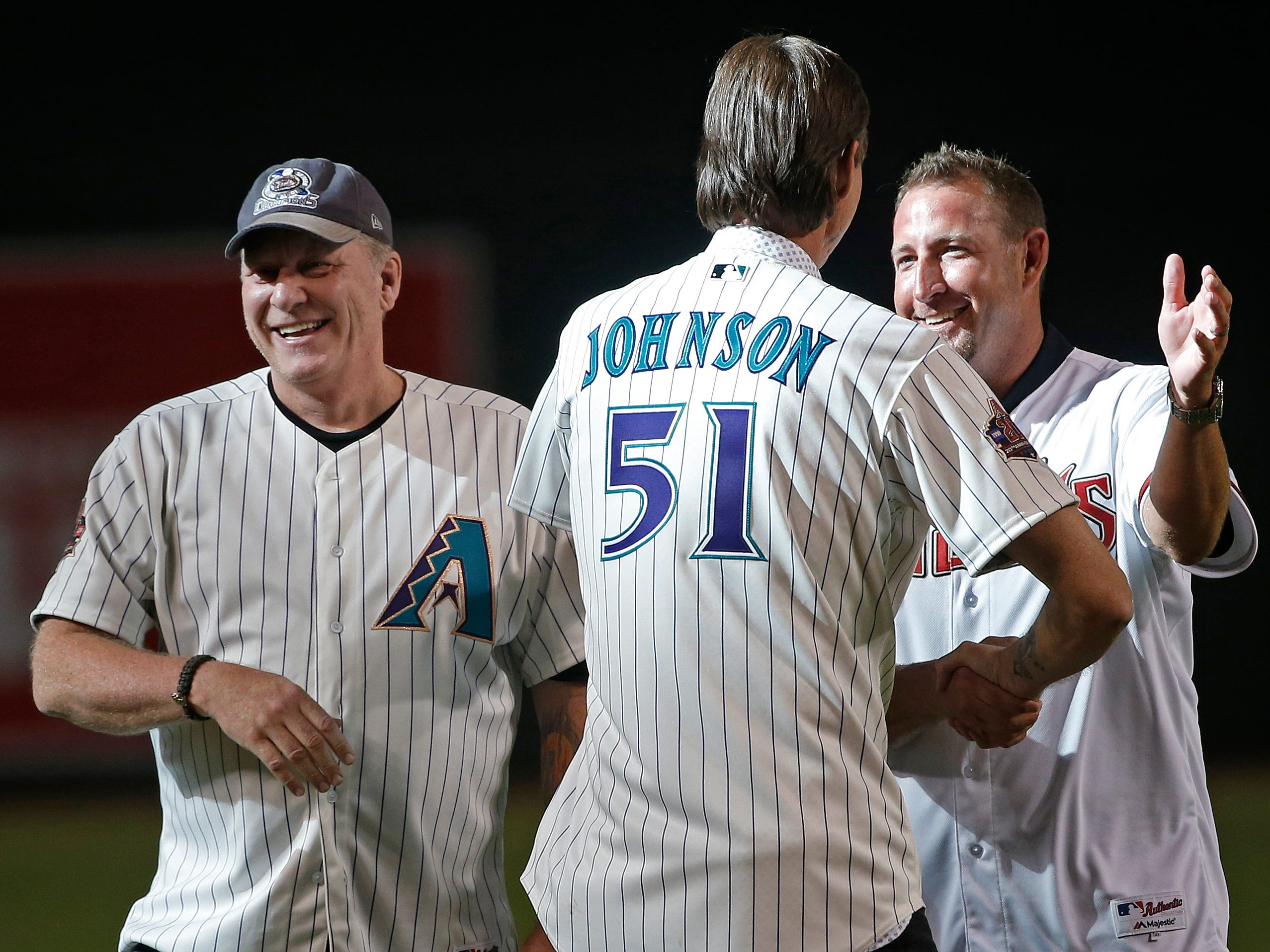 Diamondbacks Randy Johnson (51) greets pitcher Brandon Webb (R) and Curt Schilling (L) as the group was chosen for the Diamondbacks 20th Anniversary team prior to a Diamondbacks game at Chase Field in Phoenix, Ariz. on Aug. 4, 2018.