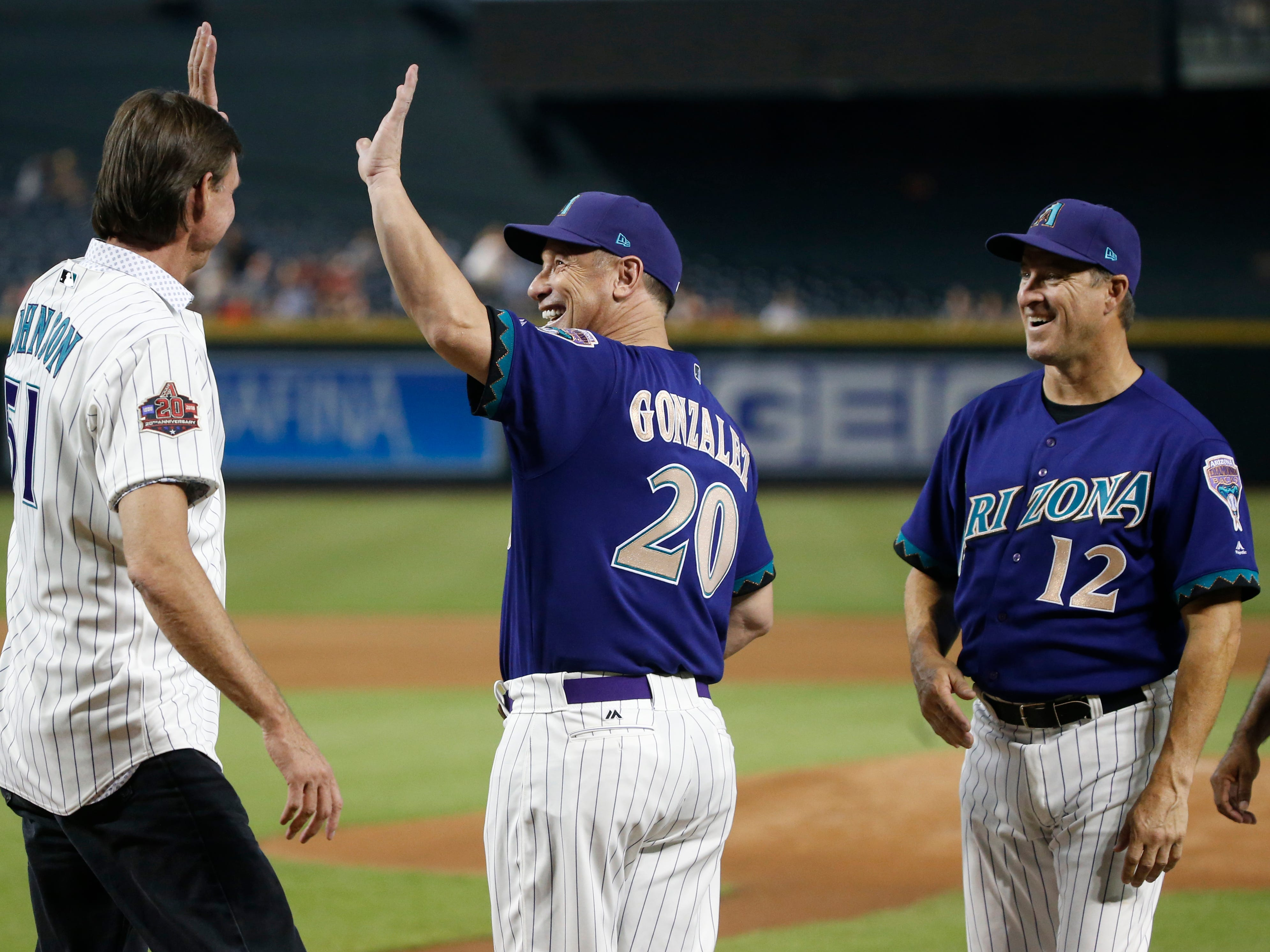 Diamondbacks Randy Johnson high-fives Luis Gonzalez (20) before the Alumni game at Chase Field in Phoenix, Ariz. on Aug. 4, 2018.